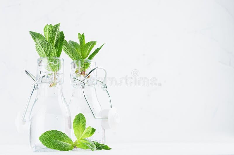 与薄荷的小树枝的透明柠檬水在软的白色木背景的葡萄酒瓶 库存照片