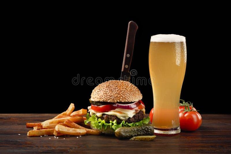 与薯条和杯的自创汉堡包在木桌上的啤酒 在汉堡黏附了一把刀子 在黑暗的背景的快餐 免版税库存图片
