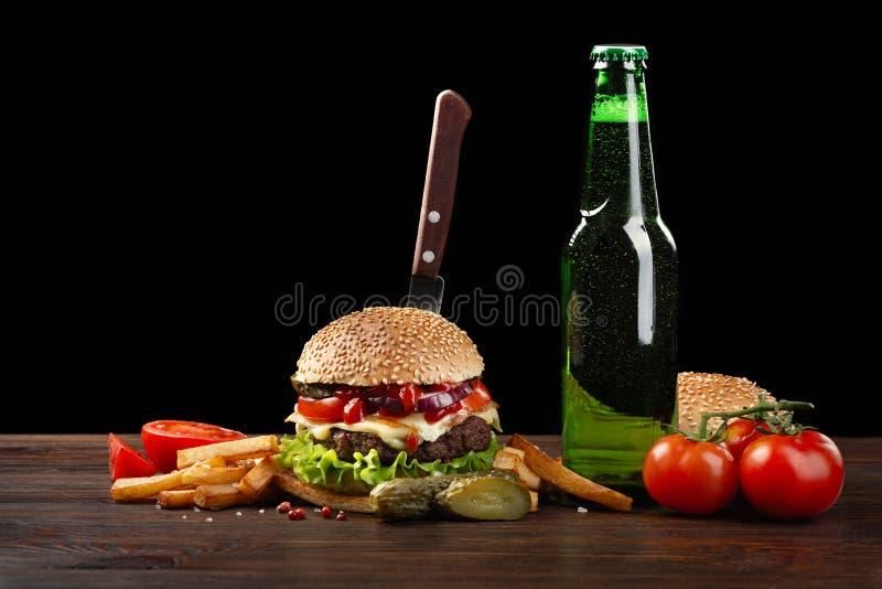 与薯条和瓶的自创汉堡包在木桌上的啤酒 在汉堡黏附了一把刀子 在黑暗的背景的快餐 免版税库存图片