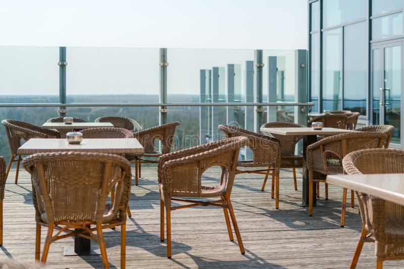与藤条柳条扶手椅子和桌的空的咖啡馆在夏天室外庭院的大阳台,自由空间 咖啡馆主持空的表 免版税库存图片