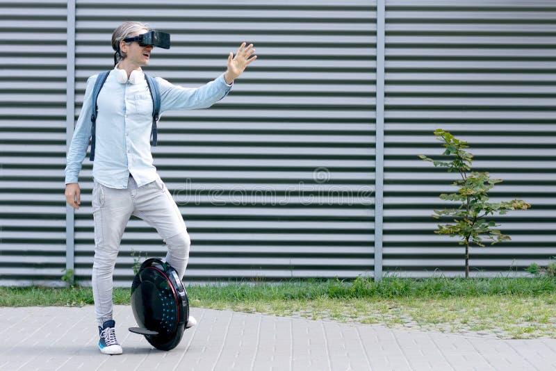 与虚拟现实玻璃和电运输的未来派人男性 库存照片