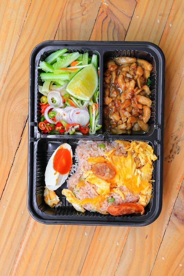 与虾酱的炒饭包括芒果,鸡蛋,猪肉,葱,在箱子黑色泰国样式食物的菜在木桌背景 免版税图库摄影