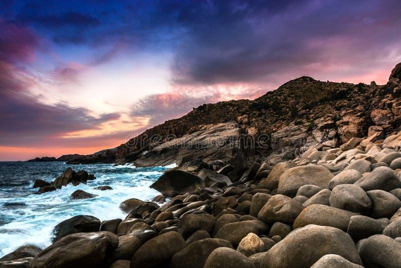 与蛋形岩石的自然海景在一个狂放的海滩、波浪和落矶山剧烈的日落的 免版税库存图片