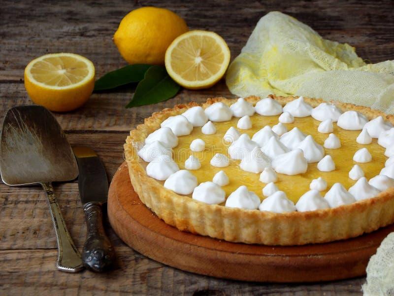 与蛋白甜饼奶油的柠檬酸的饼 在木背景的自创蛋糕 海岸线绿色水平的图象照片撒丁岛海运天空植被 免版税库存照片