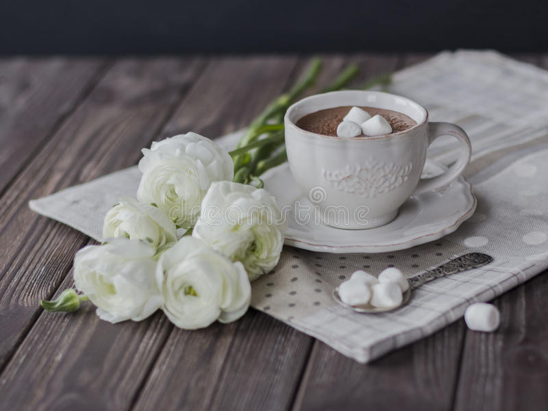 与蛋白软糖和毛茛花束的热巧克力在黑暗的桌里 库存照片