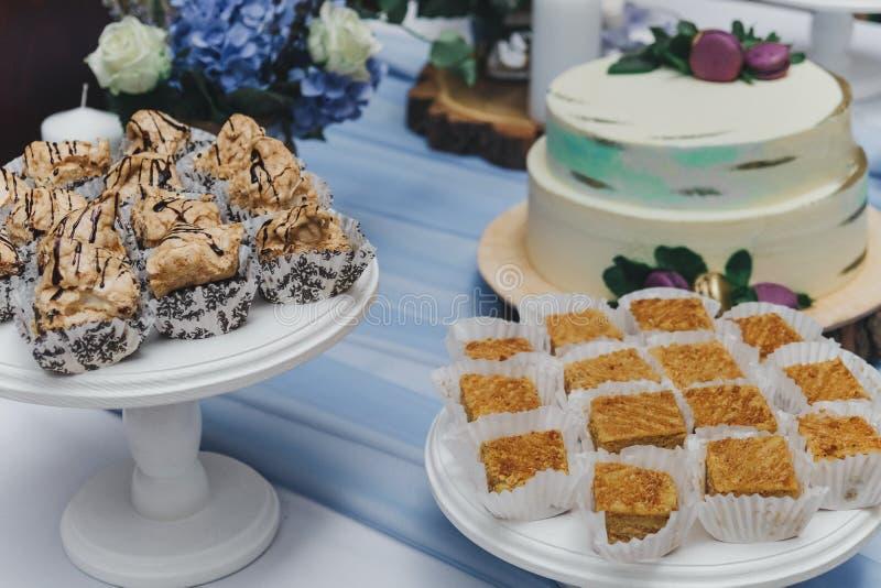 与蛋糕、杯形蛋糕、曲奇饼和通心面的表 免版税库存照片