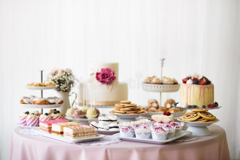与蛋糕、杯形蛋糕、曲奇饼和cakepops装载的表  库存照片