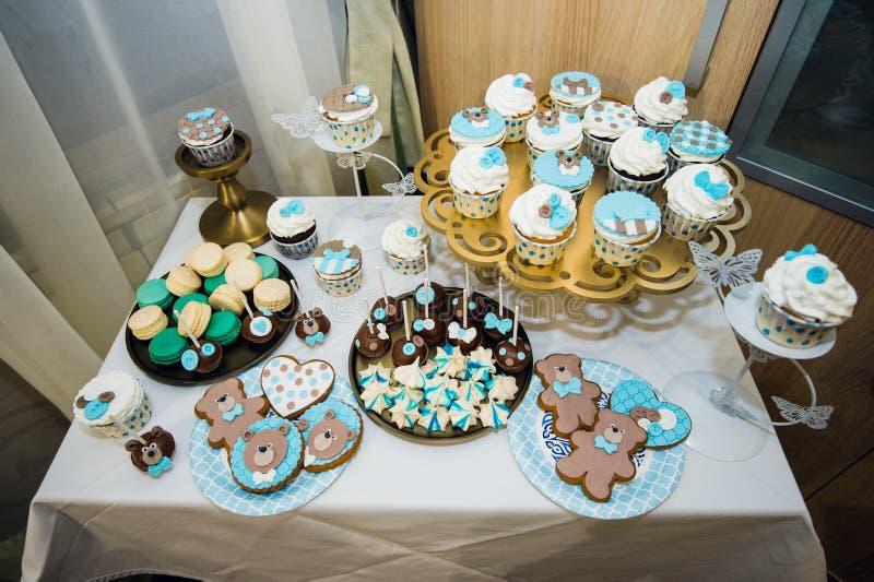与蛋糕、杯形蛋糕、曲奇饼和cakepops装载的表  免版税库存图片
