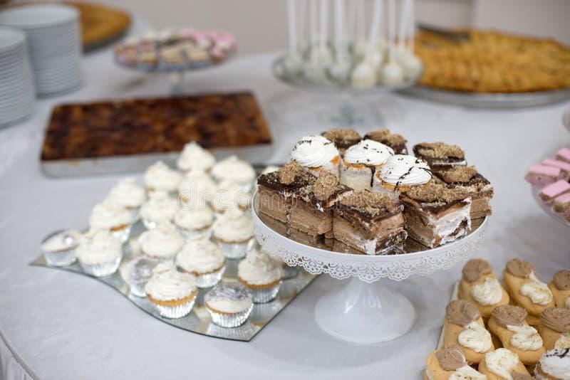 与蛋糕,杯形蛋糕,曲奇饼装载的表  库存照片