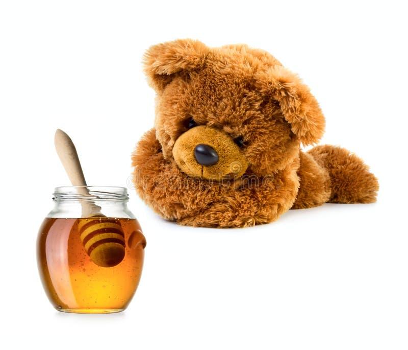 与蜂蜜瓶子的玩具熊 免版税图库摄影