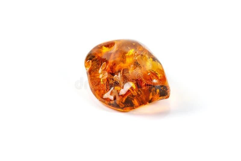 与蜘蛛的宏观琥珀色的矿物石头在白色背景 库存图片
