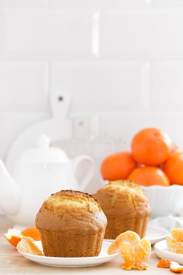 与蜜桔特写镜头的松饼在白色背景 甜可口自创烘烤 奶油被装载的饼干 库存图片