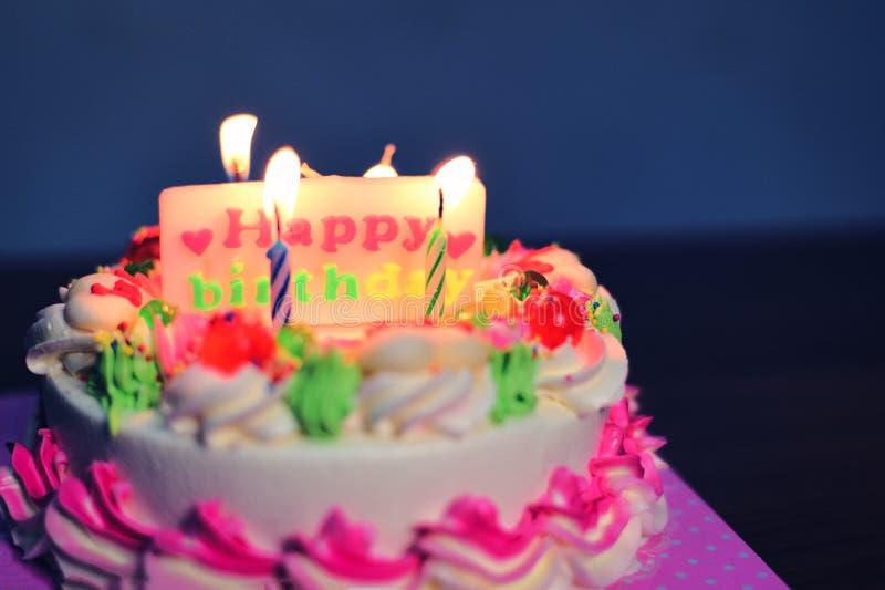 与蜡烛光的五颜六色的生日蛋糕在桌上在与生日快乐标签的晚上  免版税库存图片