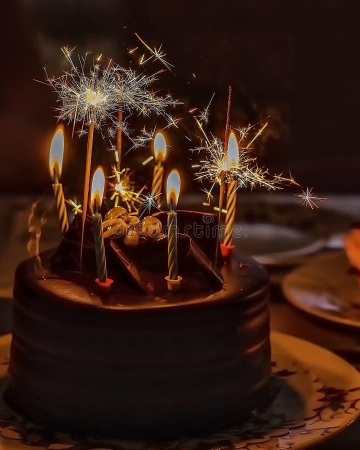 与蜡烛和闪耀的光的巧克力蛋糕 免版税库存图片