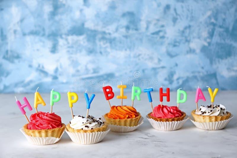 与蜡烛的五颜六色的生日杯形蛋糕在桌上 图库摄影