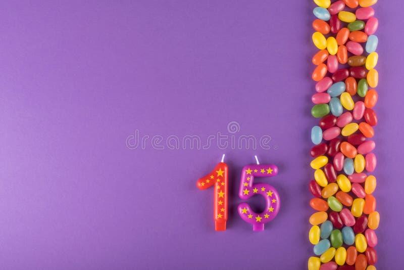 与蜡烛的五颜六色的软心豆粒糖蛋糕的 周年15年 免版税库存照片