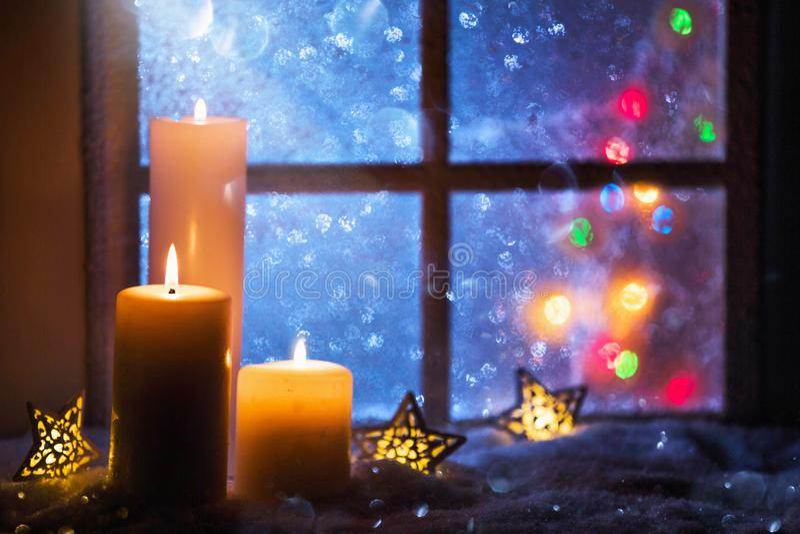 与蜡烛的冬天装饰在积雪的窗口附近 免版税库存照片