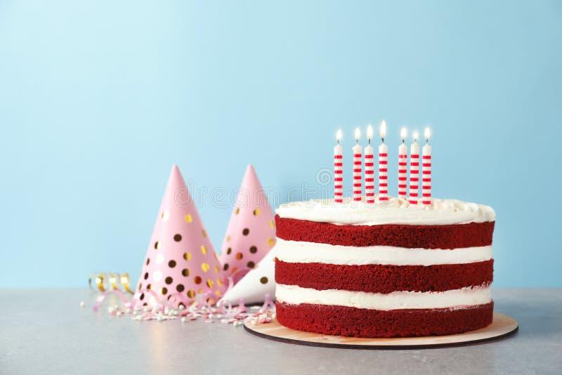 与蜡烛的可口自创红色天鹅绒蛋糕在反对颜色背景的桌上 免版税库存照片
