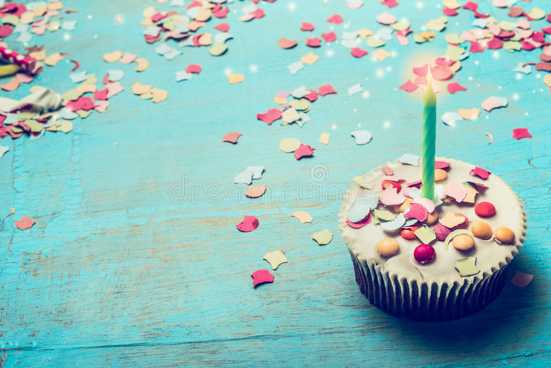 与蜡烛的在土耳其玉色破旧的别致的木背景的生日蛋糕和五彩纸屑 库存图片