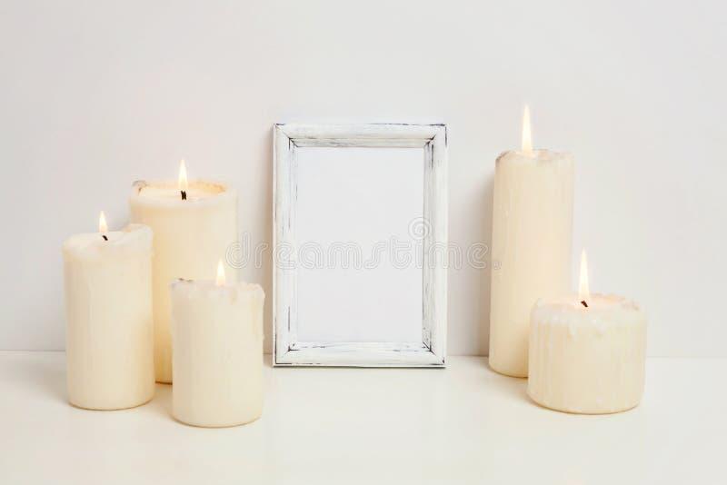 与蜡烛的垂直的框架大模型在白色墙壁附近 免版税库存照片
