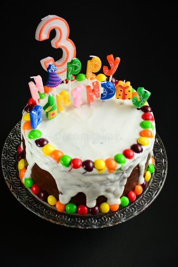 与蜡烛的生日快乐蛋糕在黑背景 免版税图库摄影