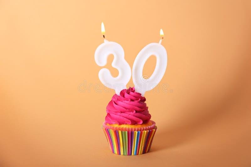 与蜡烛的生日杯形蛋糕 库存照片