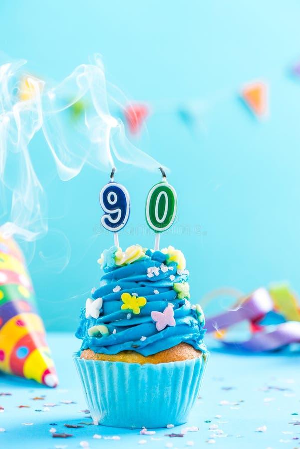 与蜡烛的第十九个第90块生日杯形蛋糕吹灭 卡片大模型 图库摄影
