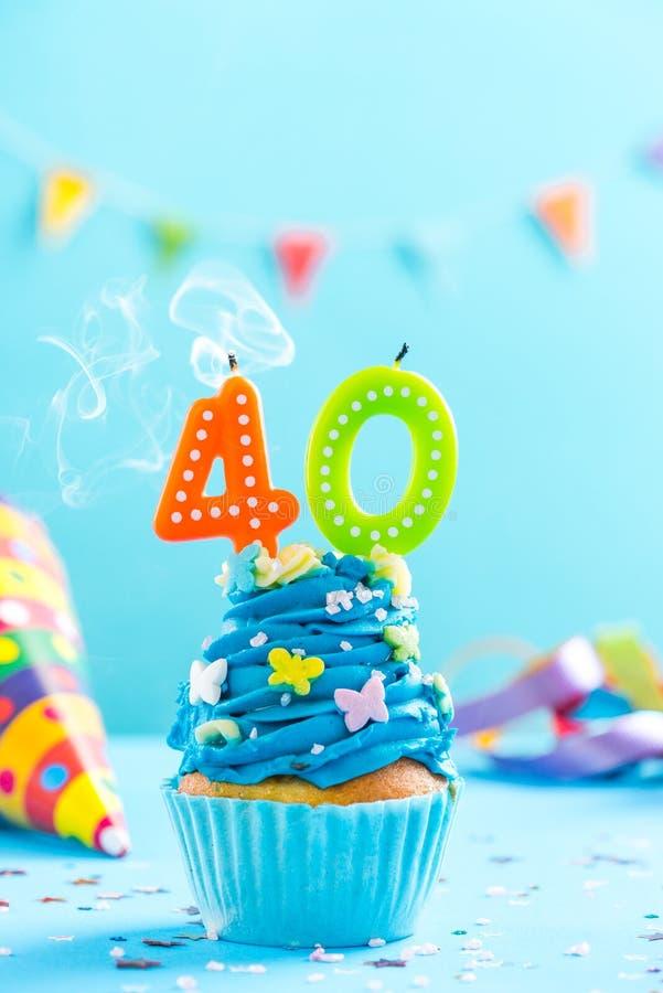 与蜡烛的第四十块第40块生日杯形蛋糕吹灭 卡片大模型 免版税库存照片