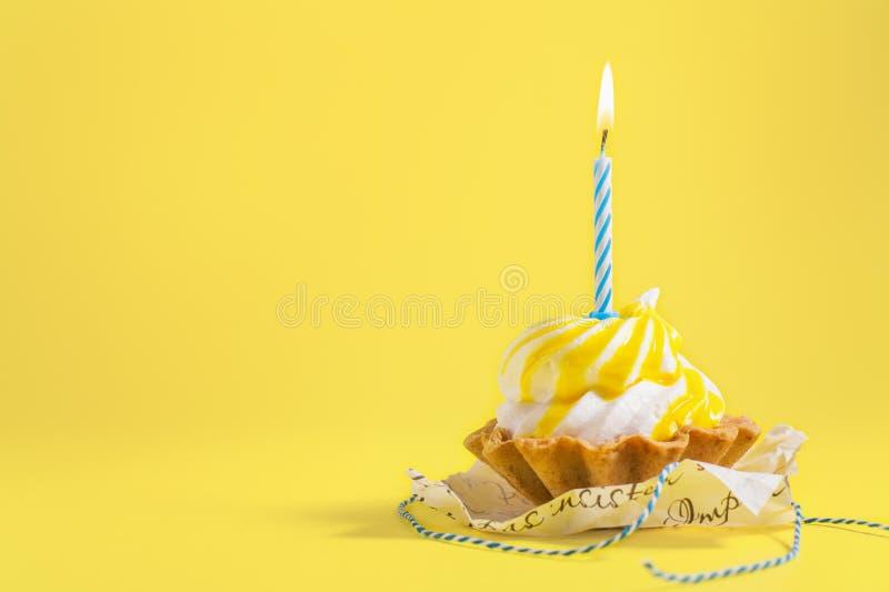 与蜡烛的鲜美生日杯形蛋糕在与拷贝空间的黄色背景 在颜色背景的可口松饼 免版税库存图片
