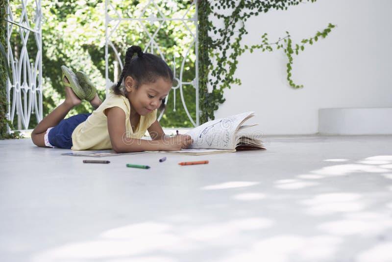 与蜡笔的女孩图画,当说谎在门廊时 免版税图库摄影