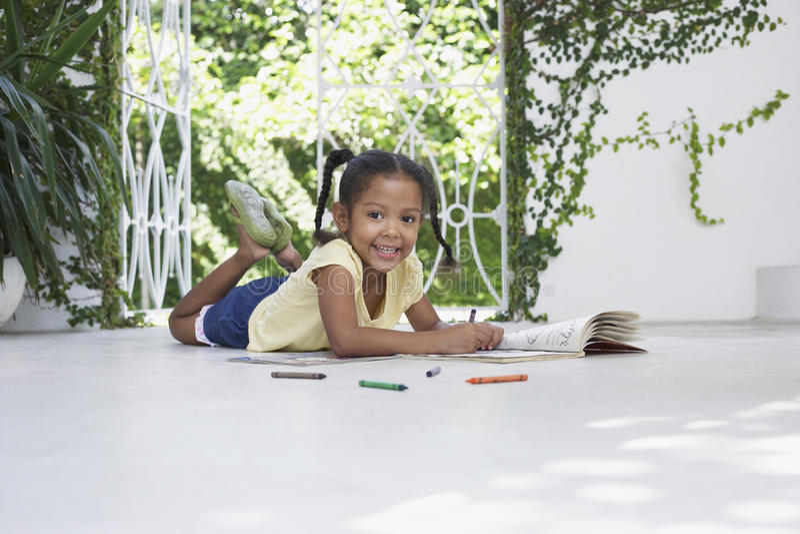 与蜡笔的女孩图画,当说谎在门廊时 库存照片