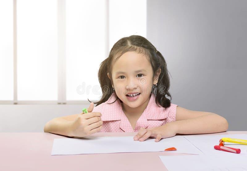 与蜡笔的愉快的亚洲女孩图画 免版税库存图片
