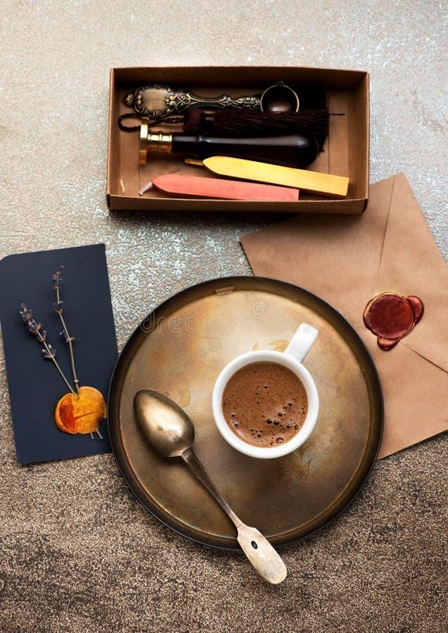 与蜡邮票的静物画用杯子咖啡,信封和蜡封印 免版税库存照片