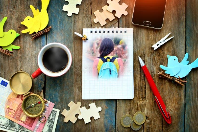 与螺纹笔记本页的土气桌与女孩旅客照片、杯子热的咖啡,智能手机、金钱、指南针、笔和其他obje 免版税库存照片