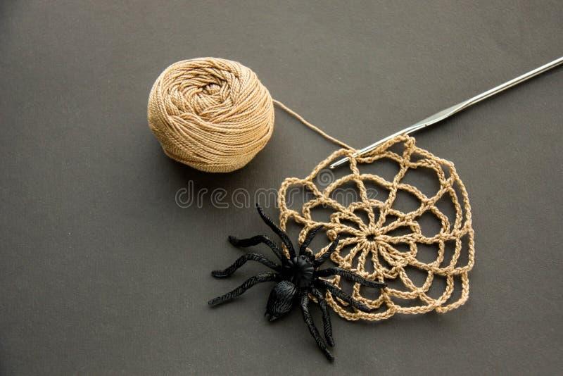 与螺纹黑橡胶蜘蛛、钩针编织和棉纱品球的钩针编织的蜘蛛网在黑纸背景的 黑暗的万圣夜octob 免版税库存图片