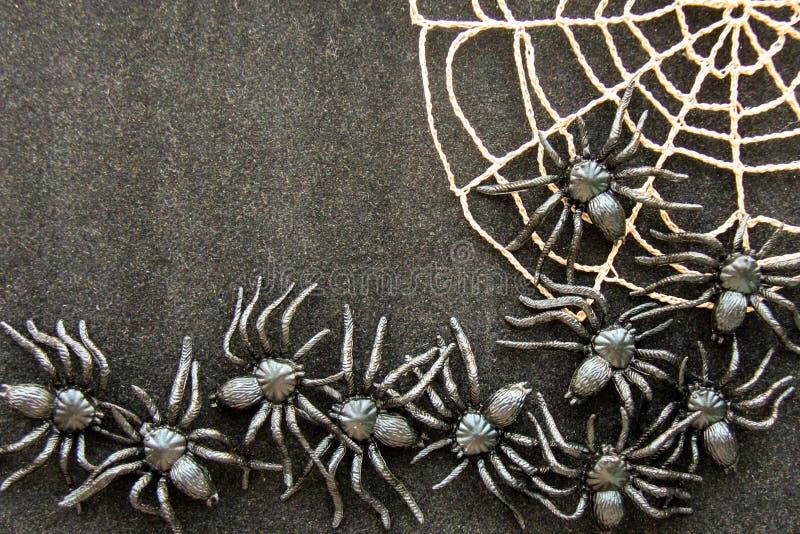 与螺纹黑橡胶蜘蛛、钩针编织和棉纱品球的钩针编织的蜘蛛网在黑纸背景的 黑暗的万圣夜octob 库存照片