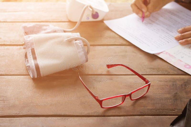 与血压显示器的红色玻璃与血压显示器,妇女写检查报告的候宰栏 免版税图库摄影