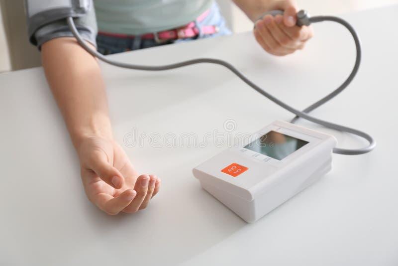 与血压计的妇女测量的血压在白色桌上 库存照片