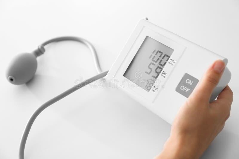 与血压计的妇女测量的血压在白色桌上 库存图片