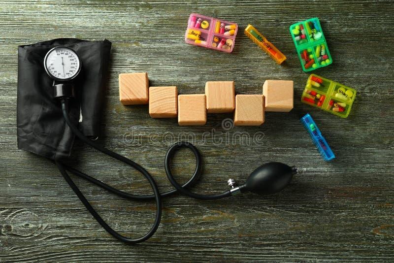 与血压计的空白的在木背景的立方体和药片 图库摄影