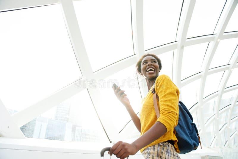 与行李和手机的愉快的非裔美国人的妇女身分在机场 库存图片