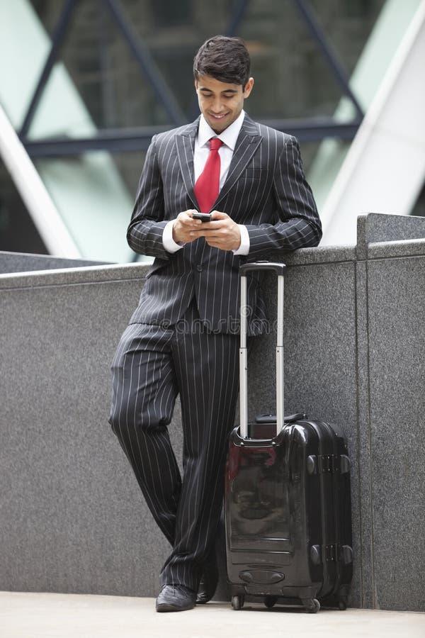 与行李袋子的年轻印地安商人使用手机 免版税库存图片
