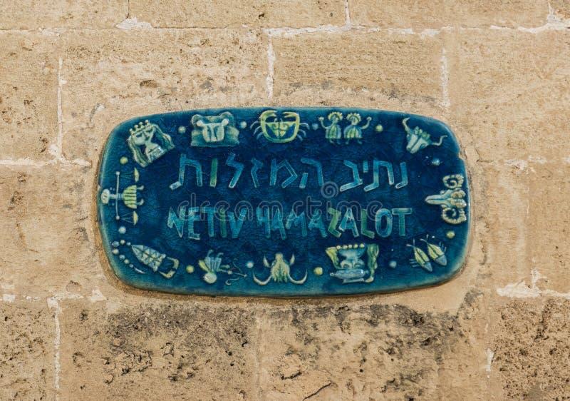 与街道的名字的一个标志在希伯来语-车道黄道十二宫的在Tel的Aviv-Yafo老城市Yafo在以色列 库存图片