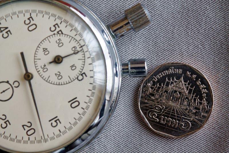 与衡量单位的泰国硬币5泰铢和秒表在灰色牛仔布背景-企业背景 库存照片