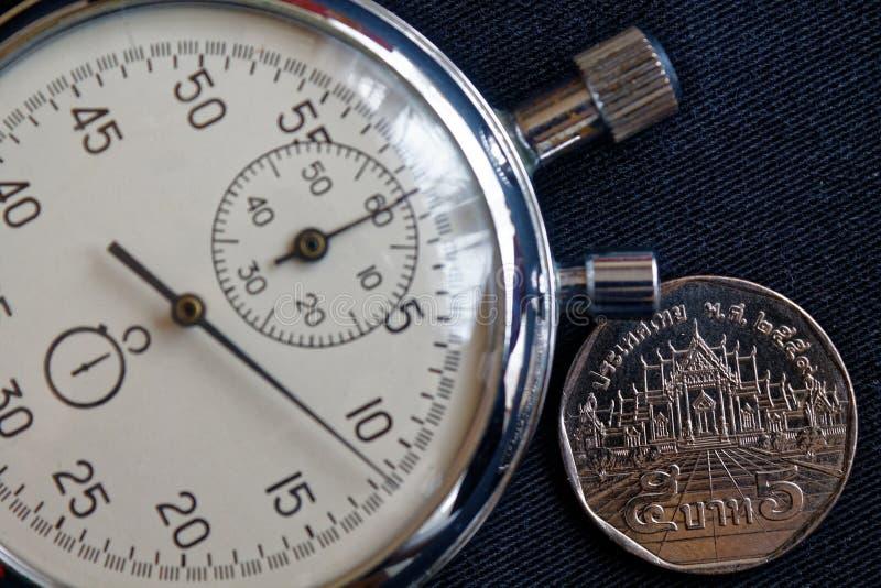 与衡量单位的泰国硬币5泰铢和秒表在老黑牛仔布背景-企业背景 免版税库存照片