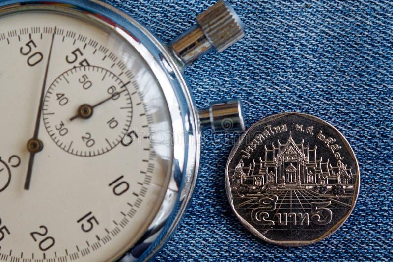 与衡量单位的泰国硬币5泰铢和秒表在蓝色牛仔裤背景-企业背景 免版税库存图片