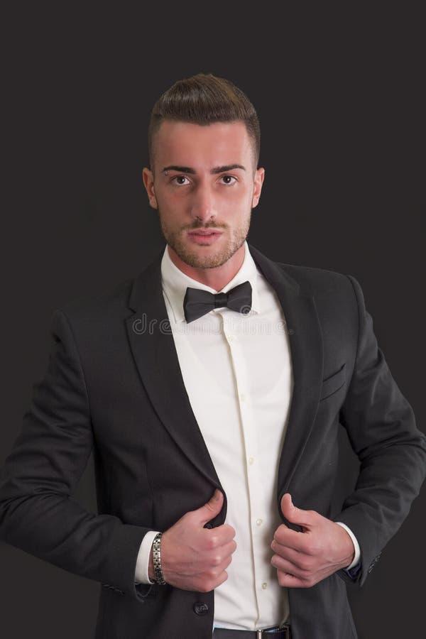 与衣服和bowtie的可爱的年轻商人 免版税库存照片