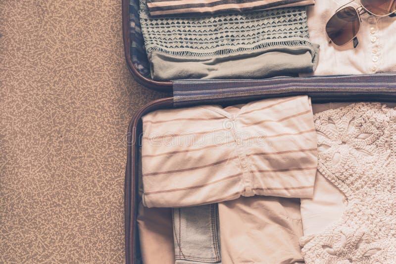 与衣物、辅助部件和护照、旅行和假期概念的开放旅客的袋子 库存照片