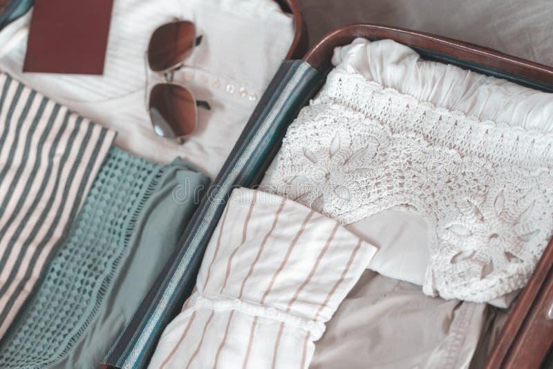 与衣物、辅助部件和护照、旅行和假期概念的开放旅客的袋子 旅行手提箱准备概念 库存照片