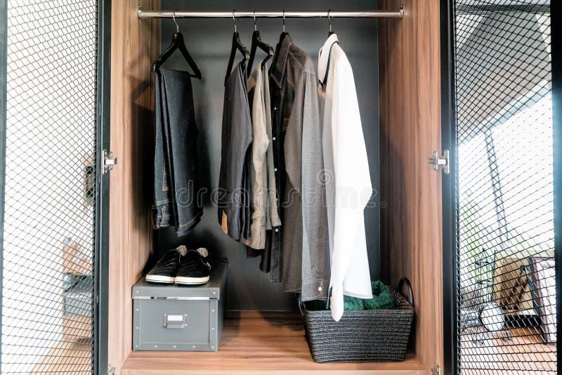 与衬衣、裤子和鞋子的现代内部人衣橱在shel 库存照片